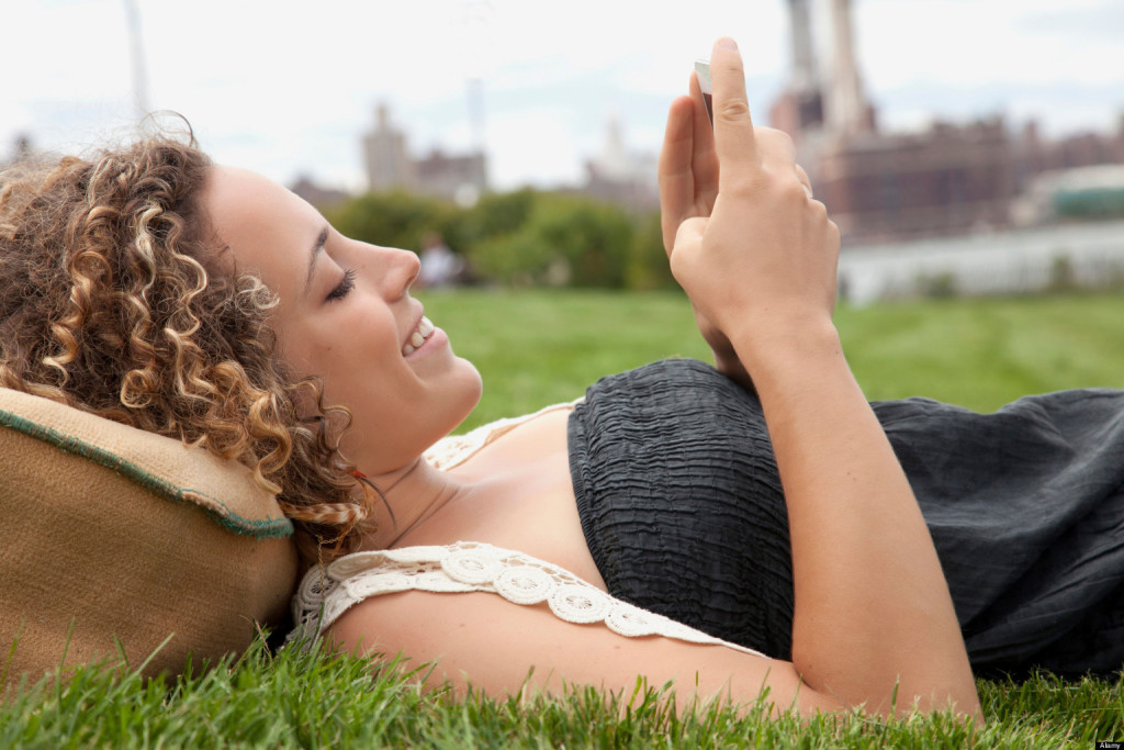 CX12Y1 Young woman lying on grass and looking at smartphone